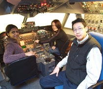 Photo of aircraft engineering students Aneja Mullenkuzhyil Jose, left, Lauren Clark and Peter Mok testing out the new Boeing 747 fixed-based simulator.