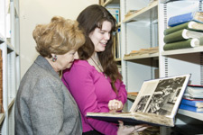 Ruth Leon and Kingston University archivist Katie Giles view a book from The Sheridan Morley Theatre Collection.